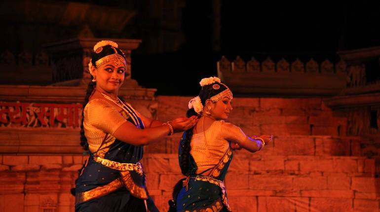 Kuchipudi dancer in a pair smiles at the camera while performing at the Khajuraho Dance Festival