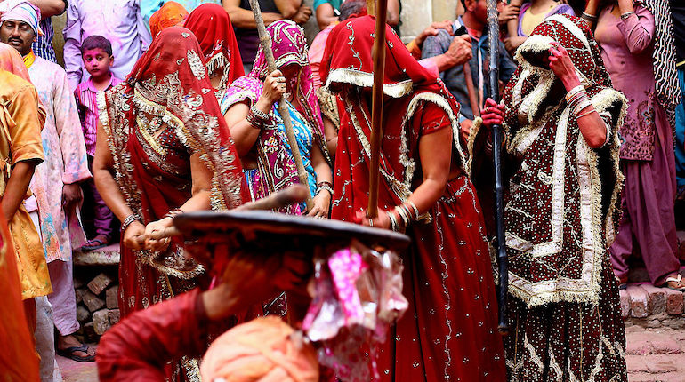 Woman in red sari playfully beats a man holding a shield during Lathmar Holi