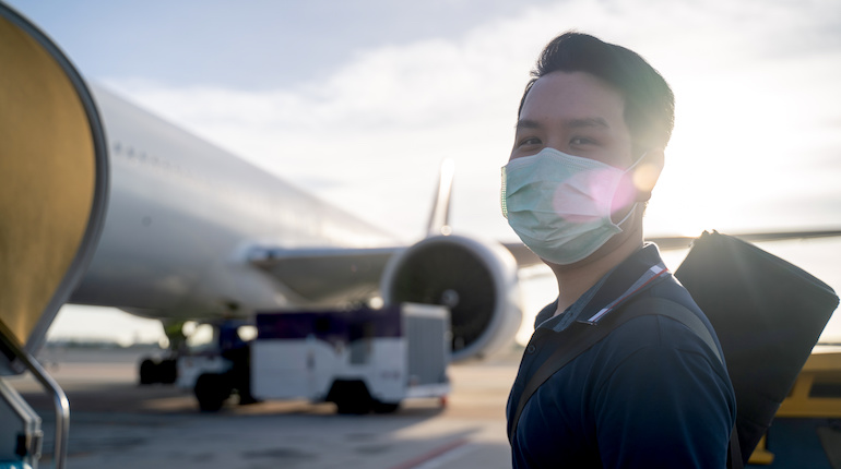Asian man wearing face mask walks to stair entering airplane, parking at remote bay located outside terminal in airport. Male passenger traveling by plane transportation during covid19 virus pandemic