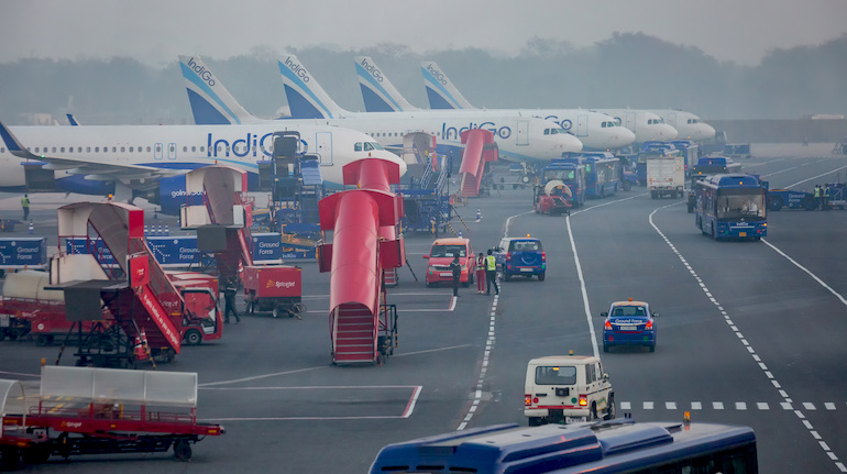 Line of IndiGo aircrafts parked along a runway in India