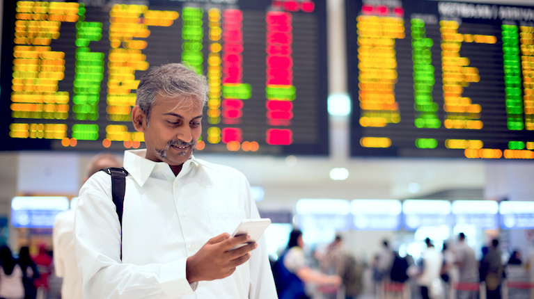 Middle-aged Indian man happily looks at his phone inside an airport with an info screen behind him