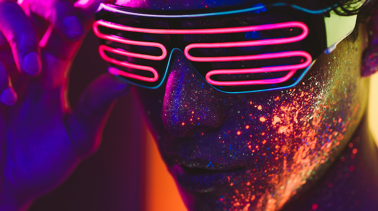 Handsome boy dancing at the rave party with fluorescent paintings on his face