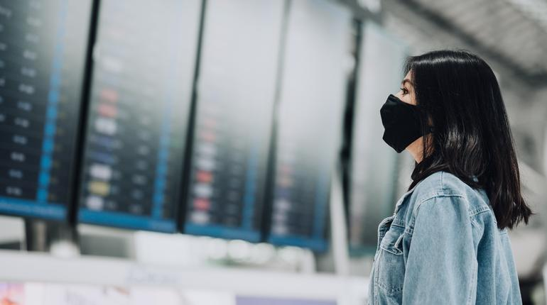 Asian woman traveler wearing mask protect from coronavirus looking flight information board display