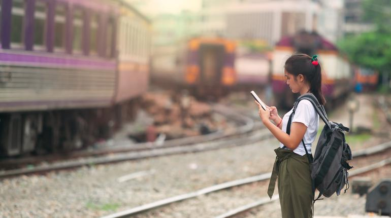 asian girl checking map on phone with backpack, travel by train, destination nature trip in summer