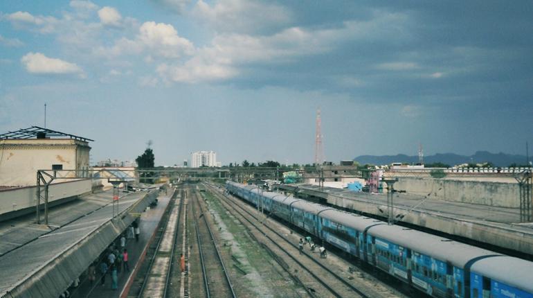 Train On Railway Tracks In City Against Sky