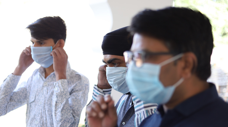 Closeup shot of three Indian men wearing a medical mask in the clinic background