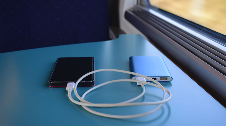 Smartphone attached to powerbank kept on a table in a moving train