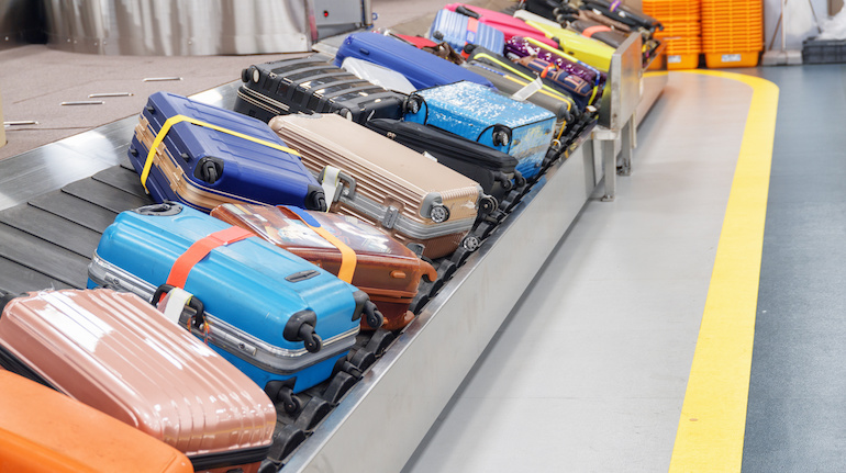 Bright suitcases lying on a conveyor belt at an airport's arrival terminal