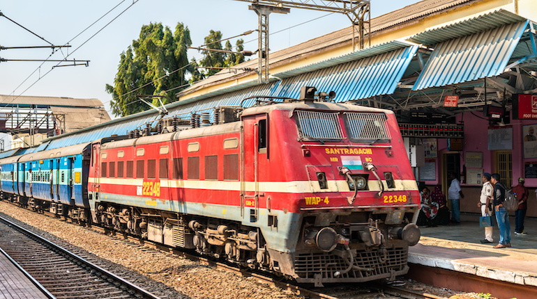 Red passenger train at a train junction in India