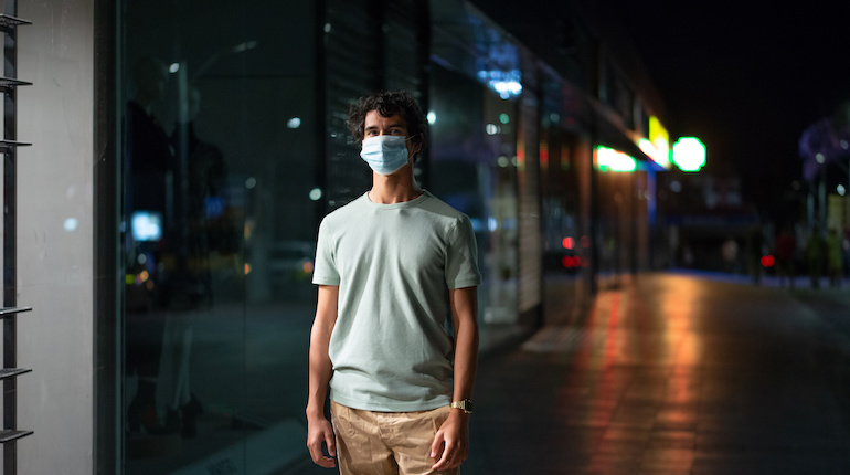 man standing on a street wearing a face mask during night curfew