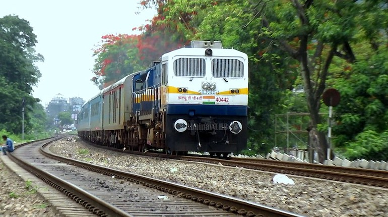 Shatabdi express travelling on train tracks through a green forested area