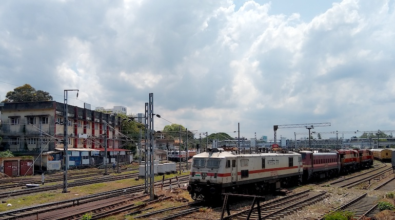 indian train waits on tracks at a station