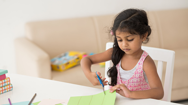 young indian girl cutting paper to make handicrafts at home