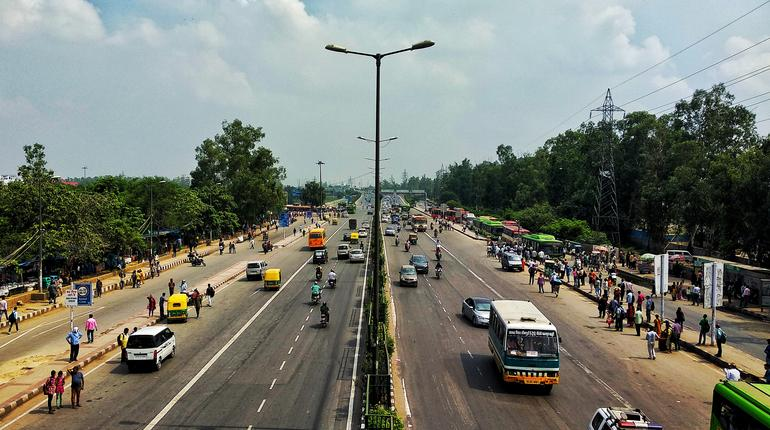 High Angle View Of People And Vehicles On Road Against Sky