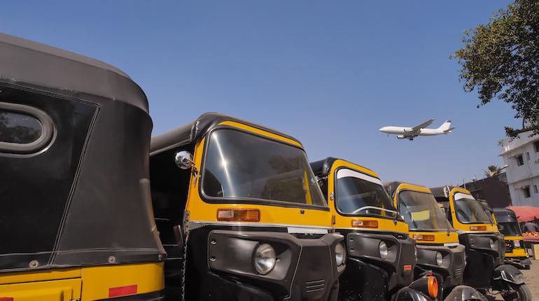 Aeroplane flies over line of autos near Mumbai Airport