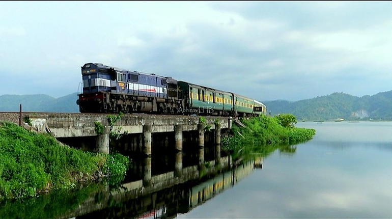 garib rath train on top of a river bridge in india
