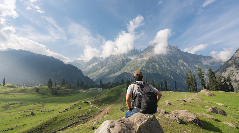 Traveller sits in front of mountain view in Himachal Pradesh