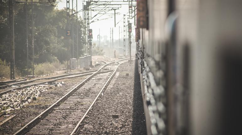People walking on the tracks between trains in India, posing a threat to trains and themselves. Danger and ignorace in india.