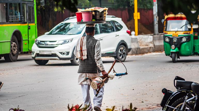 An old poor street snack food seller walks back home on a main road after a long day of hard work. Indian man carrying load on head to sell snacks on roadside. Poverty and daily wage earner labor.