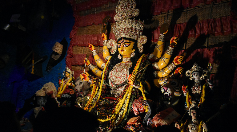 Goddess Durga idol at decorated Durga Puja pandal, shot at colored light, at Kolkata, West Bengal, India. Durga Puja is biggest religious festival of Hinduism and is now celebrated worldwide