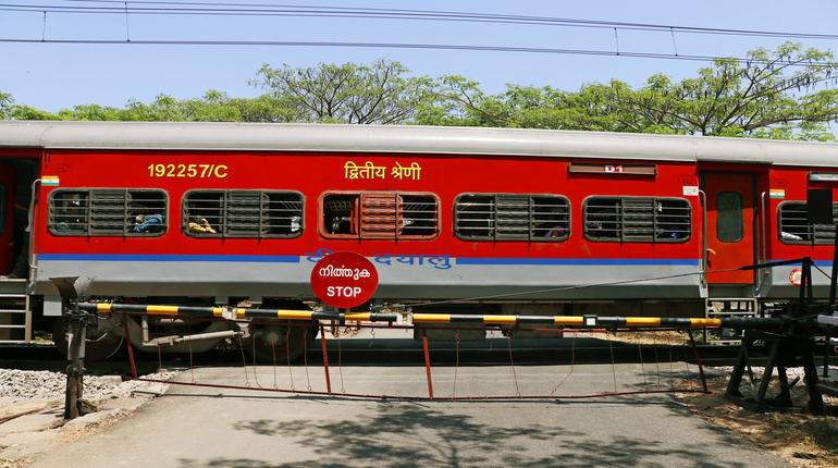 Kochi, Kerala, India -March 5, 2021 a train moving with electric support through the indian railway clossed level cross