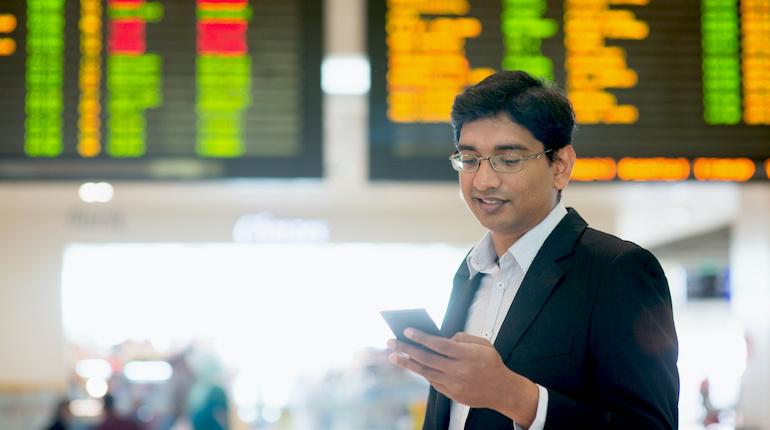 indian man checks his phone at an airport