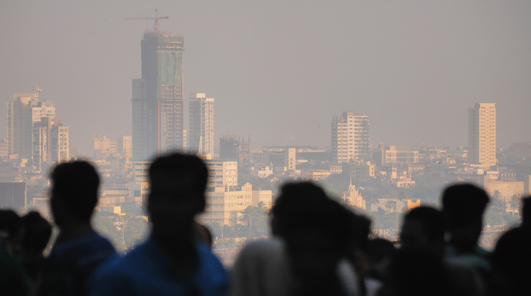Silhouette of people in Mumbai on the background of the city skyscrapers
