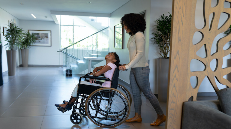 mixed race mother pushes her daughter on a wheelchair happily