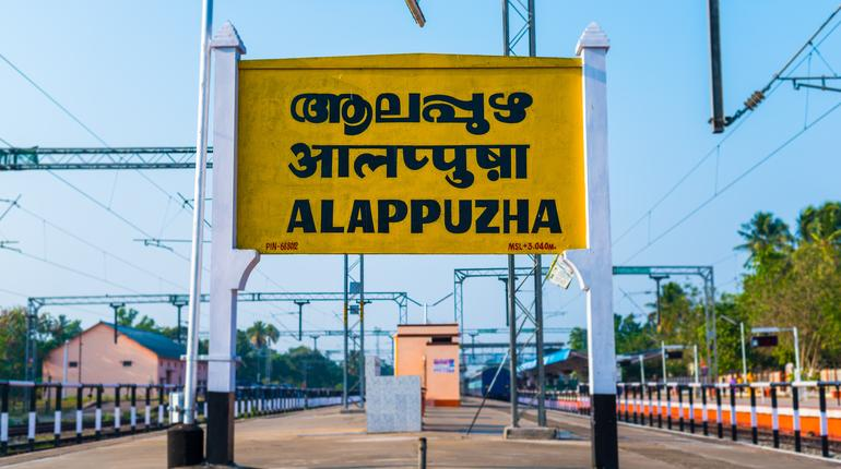 """Railroad sign """"Alappuzha"""" (Alleppey) written in Malayalam (official language of Kerala), Hindi and English on a platform of the Alappuzha (Alleppey) railway station, Kerala, India"""