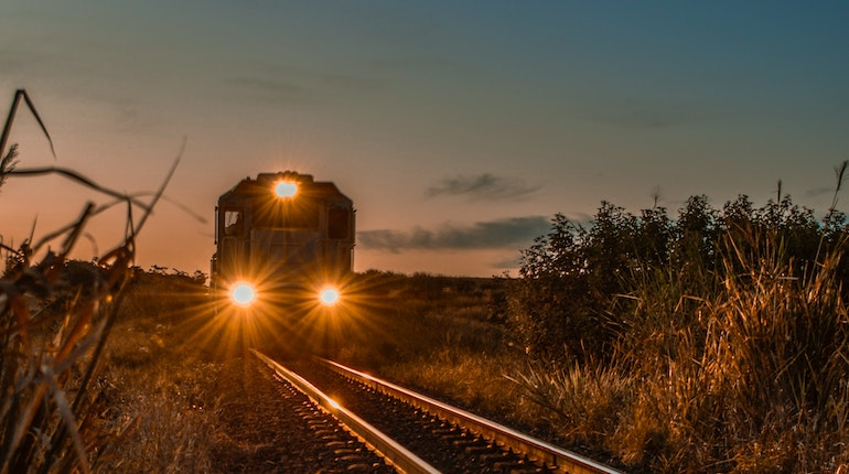train passing on tracks through open field during sunset