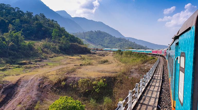 The beautiful multicolored train taking a turn on the mountainous terrain full of natural beauty and blue sky. Haflong, Assam, Northeast, India